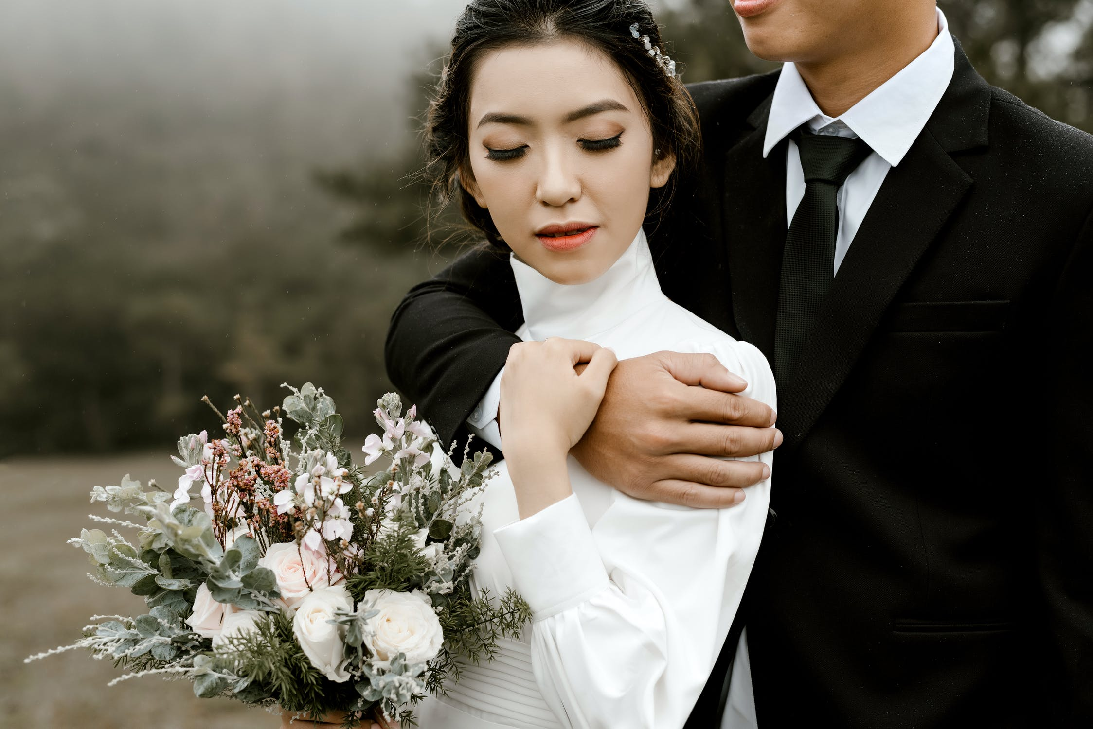 A couple on their wedding day. Man in suit has his arm wrapped protectively around his bride who is holding a bouquet.